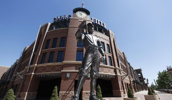 """The bronze statue entitled """"The Player,"""" by sculptor George Lundeen stands in front of the main gate of Coors Field, home of Major League Baseball's Colorado Rockies, Tuesday, June 23, 2020, in Denver. The league is waiting for the players' union to respond to whether it will agree to health protocols for a 60-game regular-season slate and if players will report for training camp by July 1. (AP Photo/David Zalubowski)  **FILE**"""
