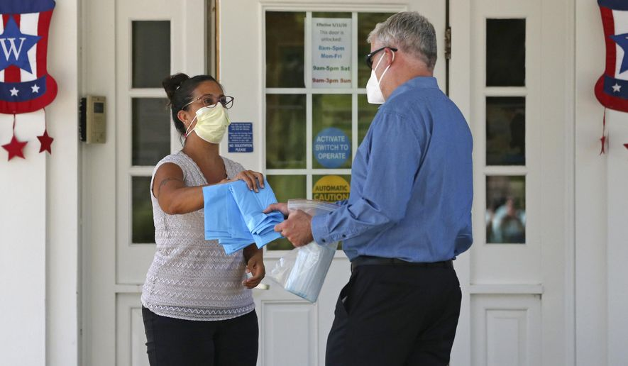Brendan Williams, president of the New Hampshire Health Care Association, right, is handed gowns and masks which were received in a shipment from the federal government, by an employee at the Webster at Rye senior care center on Wednesday, July 1, 2020, in Rye, N.H. Isolation gowns with no sleeve openings for hands, child-sized gloves and surgical masks with ear loops that break when stretched make up the bulk of the personal protective equipment recently sent by the Federal Emergency Management Agency to New Hampshire nursing homes, according to Williams. The facility is not using the items they received from FEMA. (AP Photo/Charles Krupa)