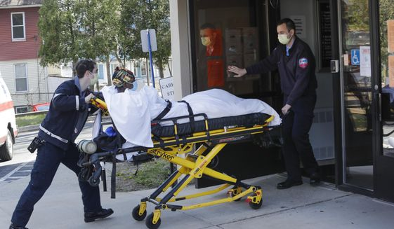 FILE - In this April 22, 2020, file photo medical workers bring a patient to the Northbridge Health Care Center in Bridgeport, Conn. A report from Senate Democrats finds that the Trump administration was slow to comprehend the scale of COVID-19's impact on nursing homes and a disjointed federal response only compounded the devastating toll. (AP Photo/Frank Franklin II)