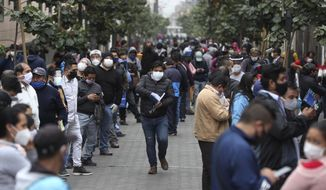 People wait in line for some businesses to reopen in downtown Lima, Peru, Wednesday, July 1, 2020. Major cities including the capital, will begin allowing for public transportation and certain businesses to reopen, but will still restrict the movement of the elderly and young children. (AP Photo/Martin Mejia)