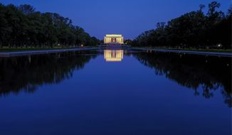 The Lincoln Memorial is reflected in the still waters of the reflecting pool on the National Mall in Washington before dawn, Wednesday, April 29, 2020. (AP Photo/J. David Ake)