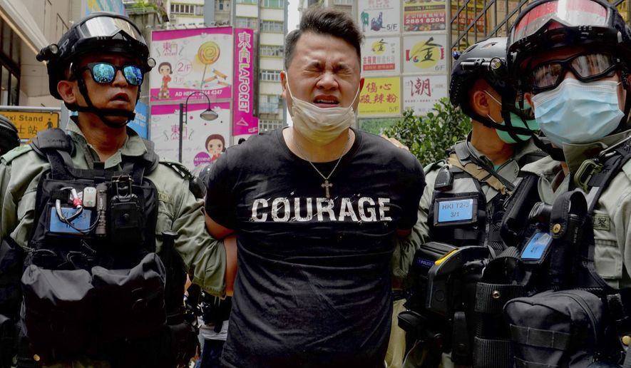 Police detain a protester after being sprayed with pepper spray during a protest in Causeway Bay before the annual handover march in Hong Kong, Wednesday, July 1, 2020. A new security law in effect in Hong Kong that limits civil liberties has prompted the Canadian government to suspend its extradition treaty with the city. (AP Photo/Vincent Yu)  **FILE**