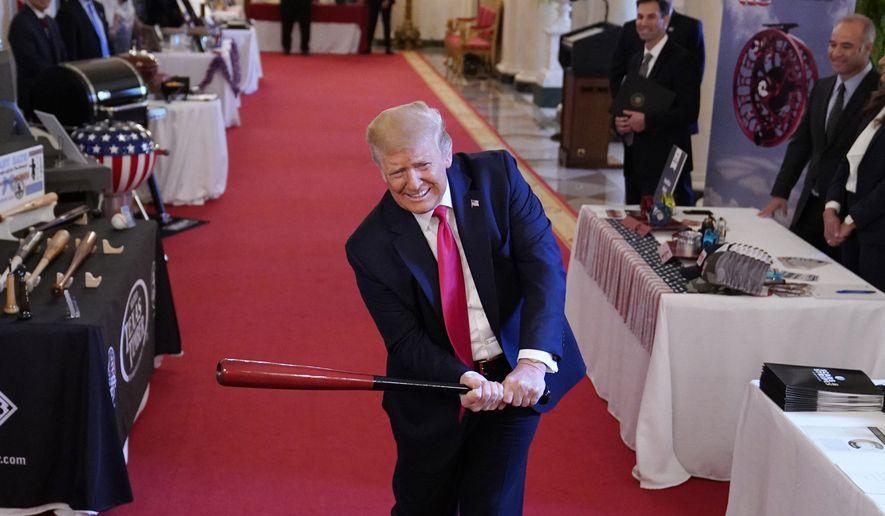 President Donald Trump swings a baseball bat during the Spirit of America Showcase at the White House, Thursday, July 2, 2020, in Washington. (AP Photo/Evan Vucci)