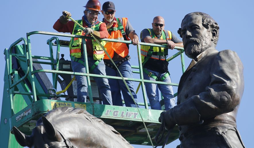 An inspection crew from the Virginia Department of General Services take measurements as they inspect the statue of Confederate General Robert E. Lee on Monument Avenue Monday June. 8, 2020, in Richmond, Va. Virginia Gov. Ralph Northam has ordered the removal of the statue. (AP Photo/Steve Helber)