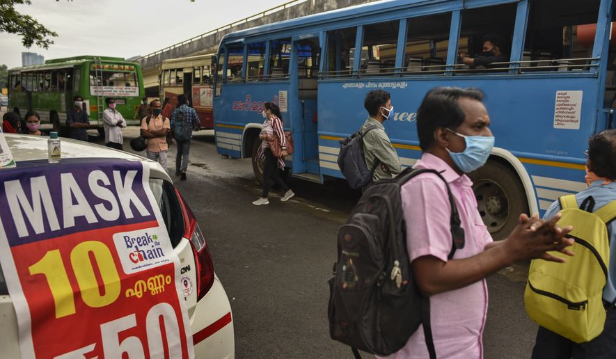 A banner displaying masks for sale stands on a car owned by a cab driver who has been out of work due to the COVID-19 pandemic and now selling face masks, as a man uses a hand sanitizer as a precaution against the coronavirus as he awaits bus in Kochi, Kerala state, India, Thursday, July 2, 2020. (AP Photo/R S Iyer)