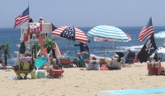 Flags line the beach in Belmar, N.J., on June 28, 2020. With large crowds expected at the Jersey Shore for the July Fourth weekend, some are worried that a failure to heed mask-wearing and social distancing protocols could accelerate the spread of the coronavirus. (AP Photo/Wayne Parry) **FILE**
