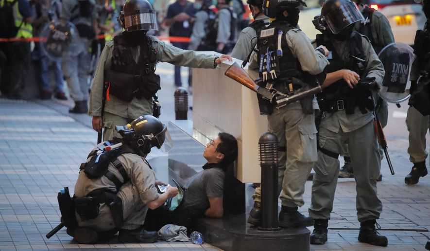 Police detained a protester during a march marking the anniversary of the Hong Kong handover from Britain to China, Wednesday, July. 1, 2020, in Hong Kong. Hong Kong marked the 23rd anniversary of its handover to China in 1997 just one day after China enacted a national security law that cracks down on protests in the territory. (AP Photo/Kin Cheung)