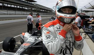 FILE - In this Friday, May 19, 2006 file photo, Indy Racing League driver Townsend Bell dons his helmet before practicing for the 90th running of the Indianapolis 500 at the Indianapolis Motor Speedway in Indianapolis.  NBC Sports analyst Townsend Bell will have his own unique double duty Saturday, July 4, 2020 when he calls the IndyCar race at Indianapolis Motor Speedway and then flies to Daytona International Speedway to compete in the IMSA sports car race.  (AP Photo/Tom Strattman, File)