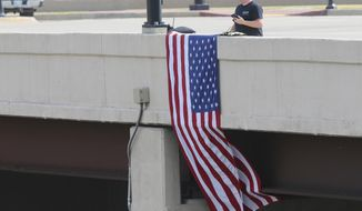 Brian Anderson holds a flag on the Lewis bridge as the body of Sgt. Craig Johnson is transported with a processional of police cars in Tulsa, Okla., Wednesday, July 1, 2020. (Tom Gilbert/Tulsa World via AP)