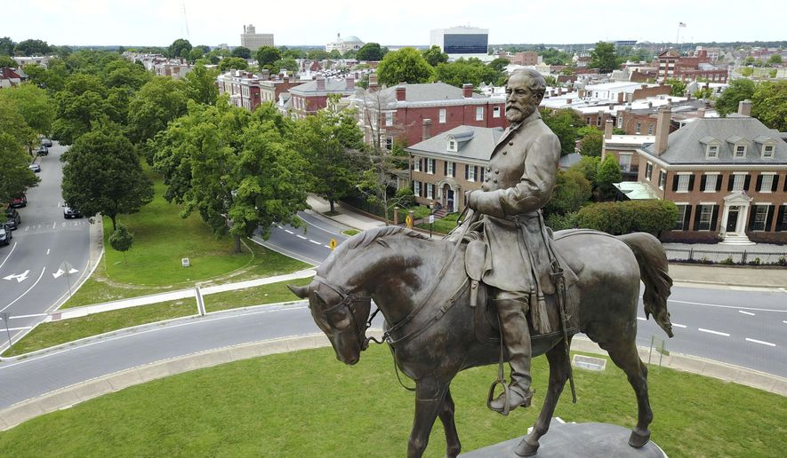 This Tuesday, June 27, 2017, file photo shows a statue of Confederate General Robert E. Lee in the middle of a traffic circle on Monument Avenue in Richmond, Va. Just a little over a month ago, the area around Richmond's iconic statue of Confederate Gen. Robert E. Lee was as quiet and sedate as the statue itself.  But since the May 25, 2020, police killing of George Floyd in Minneapolis, the area has been transformed into a bustling hub of activity for demonstrators protesting against police brutality and racism. (AP Photo/Steve Helber, File)