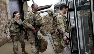 FILE-In this Saturday, Jan. 4, 2020 file photo, U.S. Army soldiers with their gear board an awaiting bus at Fort Bragg, N.C., as troops from the 82nd Airborne are deployed to the Middle East as reinforcements in the volatile aftermath of the killing of Iranian Gen. Qassem Soleimani. Members of the Army's 82nd Airborne Division from Fort Bragg, North Carolina, and the 3rd U.S. Infantry Regiment, which is based in D.C. and typically guards the Tomb of the Unknown Soldier, were mobilized last month to respond to massive protests over the treatment of Black Americans and systemic issues of police brutality.(AP Photo/Chris Seward, File)