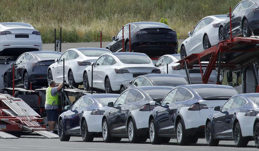 FILE - In this May 13, 2020, file photo, Tesla cars are loaded onto carriers at the Tesla electric car plant in Fremont, Calif. Tesla says it delivered more electric vehicles worldwide in the second quarter than it did in the first. The increase came even though coronavirus restrictions forced it to shut down its only U.S. factory for much of the period. (AP Photo/Ben Margot, File)