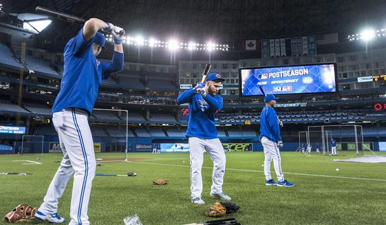 In this Oct. 7, 2015, file photo, Toronto Blue Jays Russell Martin, center, and Troy Tulowitzki, left, prepare to take batting practice during a team workout at the Rogers Centre in Toronto. All 30 Major League Baseball teams will train at their regular-season ballparks for the pandemic-shortened season after the Blue Jays received a Canadian federal government exemption on Thursday, July 2, 2020, to work out at Rogers Centre. Toronto will move camp from its spring training complex in Dunedin, Fla., where players reported for intake testing. The Blue Jays will create a quarantine environment at Rogers Centre and the adjoining Toronto Marriott City Centre Hotel which overlooks the field. (Darren Calabrese/The Canadian Press via AP, File)  **FILE**