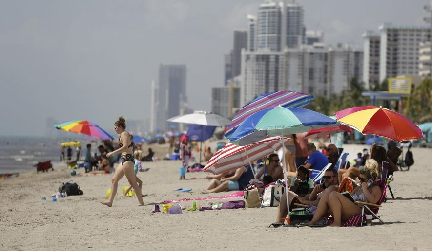 People sit on Hollywood Beach during the new coronavirus pandemic, Thursday, July 2, 2020, in Hollywood, Fla. In hard-hit South Florida, beaches from Palm Beach to Key West will be shut down for the Fourth of July holiday weekend. (AP Photo/Lynne Sladky)