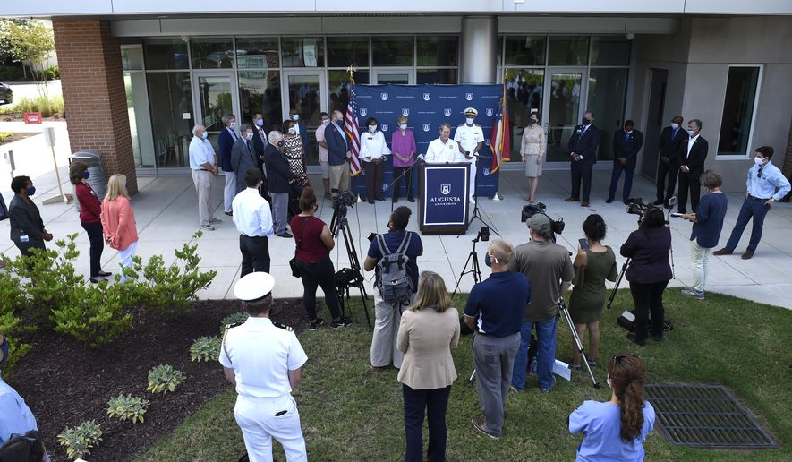 """Georgia Gov. Brian Kemp, at lectern, speaks at the Georgia Cancer Center in Augusta, Ga., Thursday, July 2, 2020, as part of his """"Wear a Mask"""" Fly-Around Tour to promote the wearing of masks as COVID numbers rise in Georgia. (Michael Holahan/The Augusta Chronicle via AP)"""