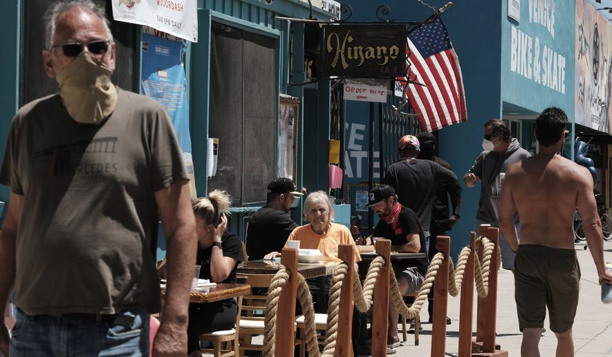 Restaurant patrons sit at an outside seating area as pedestrians pass by in the Venice beach area of Los Angeles on Friday, July 3, 2020. California took a big step back in reopening its economy as Gov. Gavin Newsom shut down bars, wineries, museums, movie theaters and inside restaurant dining across most of the state for three weeks amid troubling increases in coronavirus cases and hospitalizations. (AP Photo/Richard Vogel)