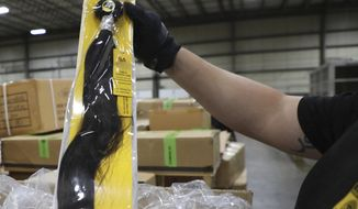 In this June 29, 2020, photo provided by U.S. Customs and Border Protection, a field operations officer inspects a suspect hair accessory at a centralized exam station in Newark, N.J. On Wednesday, July 1, 2020, U.S. Customs and Border Protection detained a shipment of weaves believed to be made in a Chinese detention camp. The shipment is suspected to be human hair. Some information on the package was blurred by the source. (U.S. Customs and Border Protection via AP)