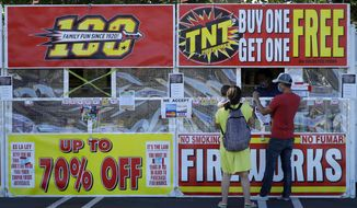 People purchase fireworks on Thursday, July 2, 2020, in Dublin, Calif. For many Americans, the Fourth of July won't be about big festivities but setting off fireworks themselves. Hundreds of cities and towns have canceled shows Saturday because of the coronavirus pandemic, and sales of consumer fireworks are booming; though officials are concerned about fires and injuries with more pyrotechnics going off in backyards and at block parties. (AP Photo/Ben Margot)
