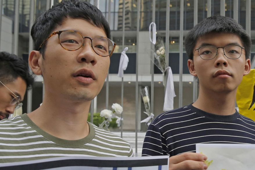 In this June 18, 2019, file photo, pro-democracy activists Nathan Law, left, and  Joshua Wong speak to the media outside a government office in Hong Kong. Prominent Hong Kong democracy activist Nathan Law has left the city for an undisclosed location, he revealed on his Facebook page shortly after testifying at a U.S. congressional hearing about the tough national security law China had imposed on the semi-autonomous territory.  In his post late Thursday, July 2, 2020, he said that he decided to take on the responsibility for advocating for Hong Kong internationally and had since left the city. (AP Photo/Kin Cheung, File)
