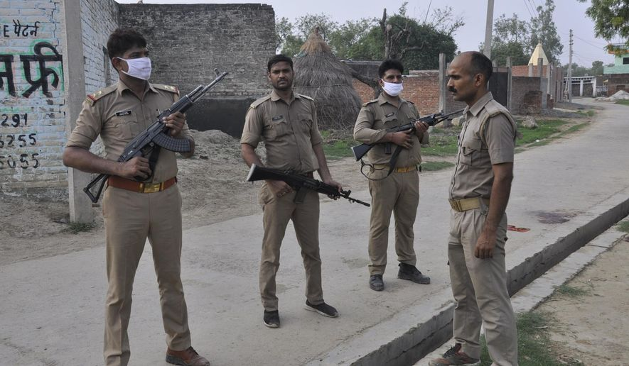 Policemen stand guard after a gang of criminals ambushed and fired on police who had come to arrest them in Kanpur, India, Friday, July 3, 2020. The criminals blocked a road with excavators and fired on the police officers from rooftops, said Awanish Awasthi, an Uttar Pradesh state government spokesman. Five officers were injured and the assailants fled before police reinforcements could reach the area, Awasthi said. (AP Photo)