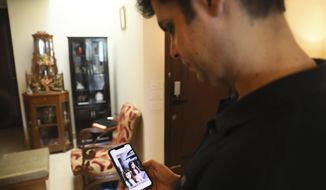 Karan Murgai, an IT management consultant for a multinational based in Dallas, shows on his phone in New Delhi, India, photograph of his daughters, who are in Dallas. Tuesday, June 30, 2020. Murgai came to Delhi in March this year after his father died. Murgai and at least 1,000 others like him, whose U.S. visas are tied to their jobs in the U.S., are now stranded in India, after an executive order signed by President Donald Trump that suspends applications for H-1B and other high-skilled work visas from abroad.(AP Photo/Manish Swarup)