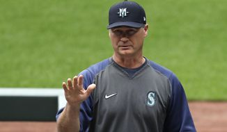 """Seattle Mariners manager Scott Servais addresses players and other team personnel before practice at a """"summer camp"""" baseball workout on their ballpark field Friday, July 3, 2020, in Seattle. (AP Photo/Elaine Thompson)"""