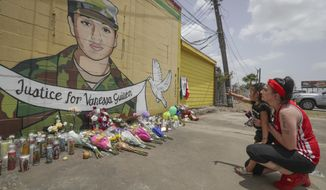 "Dawn Gomez holds her 3-year-old granddaughter, Saryia Greer, who waves at Vanessa Guillen's mural painted by Alejandro ""Donkeeboy"" Roman Jr. on the side of Taqueria Del Sol, Thursday, July 2, 2020, in Houston. Army investigators believe Guillen, a Texas soldier missing since April, was killed by another soldier on the Texas base where they served, the attorney for the missing soldier's family said Thursday. (Steve Gonzales/Houston Chronicle via AP)"