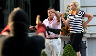 In this June 28, 2020, file photo, armed homeowners Mark and Patricia McCloskey, standing in front their house along Portland Place, confront protesters marching to St. Louis Mayor Lyda Krewson's house in the Central West End of St. Louis. (Laurie Skrivan/St. Louis Post-Dispatch via AP File)