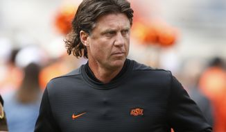 """FILE - In this Oct. 6, 2018, file photo, Oklahoma State football coach Mike Gundy runs onto the field before the team's NCAA college football game against Iowa State in Stillwater, Okla. Mike Holder, Oklahoma State's athletic director, said late Thursday, July 2, 2020, an internal review had found """"no sign or indication of racism"""" in the football program under Gundy after a number of players raised concerns. (AP Photo/Sue Ogrocki, File)"""
