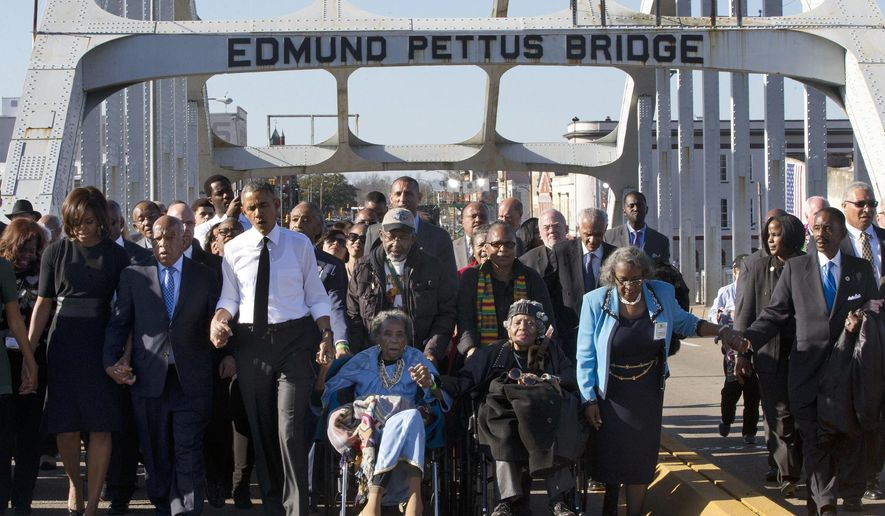 "In this March 7, 2015, file photo, singing ""We Shall Overcome,"" President Barack Obama, third from left, walks holding hands with Amelia Boynton, who was beaten during ""Bloody Sunday,"" as they and the first family and others including Rep. John Lewis, D-Ga, left of Obama, walk across the Edmund Pettus Bridge in Selma, Ala., for the 50th anniversary of ""Bloody Sunday,"" a landmark event of the civil rights movement. Some residents in the landmark civil rights city of Selma, Ala., are among the critics of a bid to rename the historic bridge where voting rights marchers were beaten in 1965. (AP Photo/Jacquelyn Martin, File)"