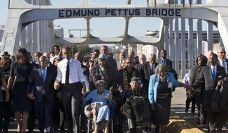"""In this March 7, 2015, file photo, singing """"We Shall Overcome,"""" President Barack Obama, third from left, walks holding hands with Amelia Boynton, who was beaten during """"Bloody Sunday,"""" as they and the first family and others including Rep. John Lewis, D-Ga, left of Obama, walk across the Edmund Pettus Bridge in Selma, Ala., for the 50th anniversary of """"Bloody Sunday,"""" a landmark event of the civil rights movement. Some residents in the landmark civil rights city of Selma, Ala., are among the critics of a bid to rename the historic bridge where voting rights marchers were beaten in 1965. (AP Photo/Jacquelyn Martin, File)"""