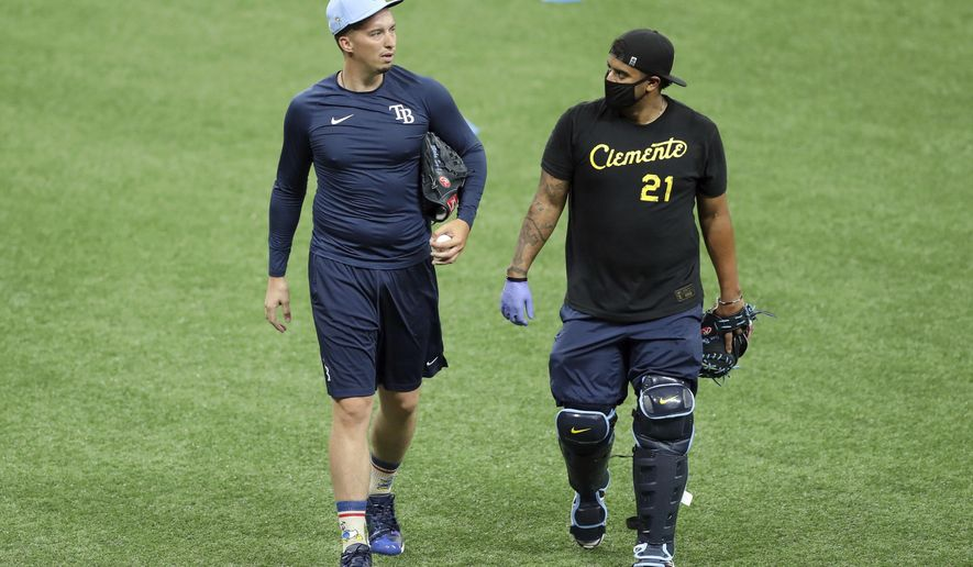 Tampa Bay Rays' Blake Snell, left, talks with bullpen catcher Jean Ramirez during baseball practice Friday July 3, 2020, in St. Petersburg, Fla. Snell made headlines in May when he said he opposed the idea of players taking further pay reductions to start the season during a pandemic — that it was not worth the health risk. But he said Friday it wasn't difficult to start playing again after the players' agreement with Major League Baseball included their full pro-rated salaries. (AP Photo/Mike Carlson)