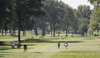 Golfers walk on the sixth fairway during the second round of the Rocket Mortgage Classic golf tournament, Friday, July 3, 2020, at the Detroit Golf Club in Detroit. (AP Photo/Carlos Osorio)