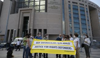 Protesters from Amnesty International stage a protest outside a court in Istanbul, Friday, July 3, 2020, where the trial of 11 prominent human rights activists for terror-related charges and adjourned proceedings was continuing. The banner reads in Turkish: 'Justice for Rights Defenders'. The closely-watched case against Amnesty International's former Turkey chairman and 10 other activists heightened concerns about Turkey's treatment of human rights defenders and helped sour Turkey's relations with European nations, notably with Germany. (AP Photo/Emrah Gurel)