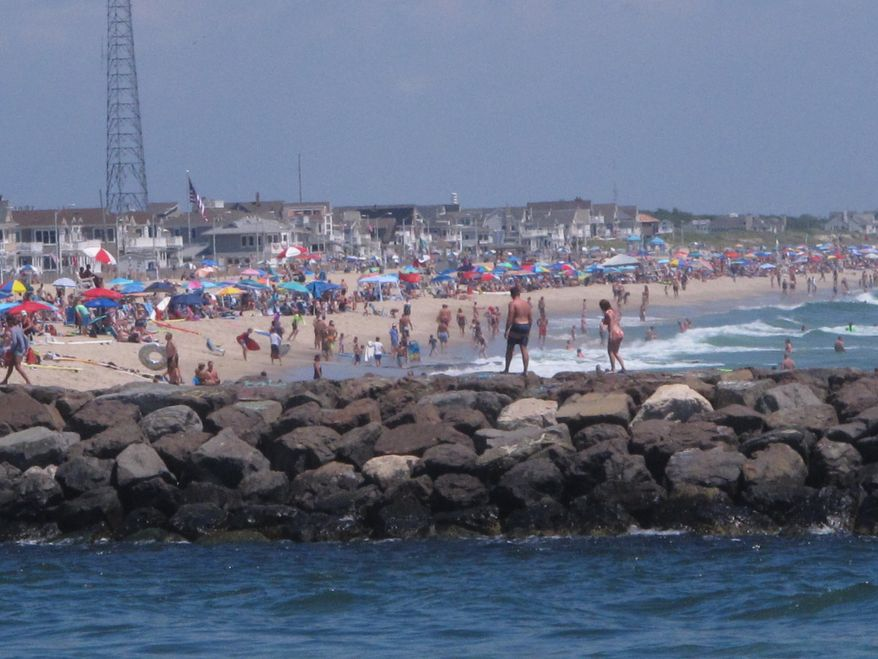 A large crowd fills the beach in Manasquan, N.J. on June 28, 2020. With large crowds expected at the Jersey Shore for the July Fourth weekend, some are worried that a failure to heed mask-wearing and social distancing protocols could accelerate the spread of the coronavirus. (AP Photo/Wayne Parry)
