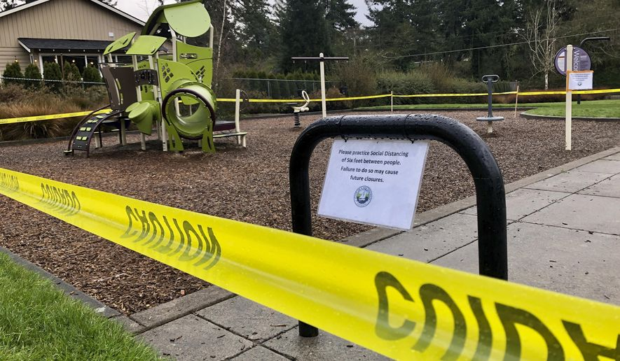 FILE - In this March 24, 2020, file photo, police caution tape surrounds a playground in Lake Oswego, Ore., during the coronavirus outbreak. Oregon health officials reported its second-highest tally of confirmed cases of COVID-19 and five additional deaths on Friday, June 26, 2020, the same day that authorities released new modeling that shows increased transmission of the coronavirus since the state began reopening in mid-May. (AP Photo/Gillian Flaccus, File)