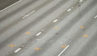 Two women were struck and critically injured where orange evidence markers are seen when a car sped through their small protest gathered on a closed Interstate 5 near the Yale Avenue on-ramp in Seattle, early Saturday July 4, 2020. Authorities say a 27-year-old man suspected of driving onto the closed freeway in Seattle early Saturday and barreling into a crowd of protesters has been arrested and booked on two counts of vehicular assault. (Bettina Hansen/The Seattle Times via AP)