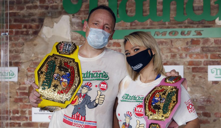 Competitive eaters Joey Chestnut, left, and Miki Sudo, right, pose for a photograph after winning their respective divisions with new world records after the Nathan's Famous July Fourth hot dog eating contest, Saturday, July 4, 2020, in the Brooklyn borough of New York. AP Photo/John Minchillo)