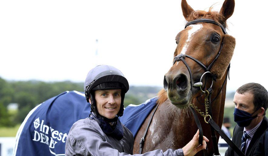 Jockey Emmet McNamara celebrates with Serpentine after winning the Investec Derby at Epsom Racecourse, in Epsom, England, Saturday, July 4, 2020. (Edward Whitaker/PA via AP)