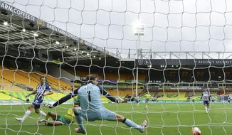 Brighton's Leandro Trossard, left, scores his side's opening goal past Norwich City's goalkeeper Tim Krul during the English Premier League soccer match between Norwich City and Brighton & Hove Albion at Carrow Road Stadium in Norwich, England, Saturday, July 4, 2020. (Richard Heathcote/Pool Photo via AP)