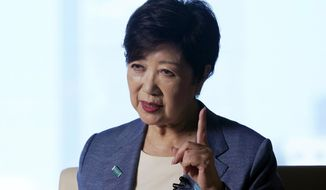 FILE - In this  June 17, 2020, file photo, Tokyo Gov. Yuriko Koike gestures while speaking during an exclusive interview with The Associated Press at her office of the Tokyo Metropolitan Government Building in Tokyo, ahead of a two-week campaigning for the Tokyo gubernatorial election. Koike is poised to be reelected in Sunday, July 5, 2020 polls, buoyed by public support for her coronavirus handling despite a recent rise in infections that has raised concerns of a resurgence of the disease. (AP Photo/Eugene Hoshiko, File)