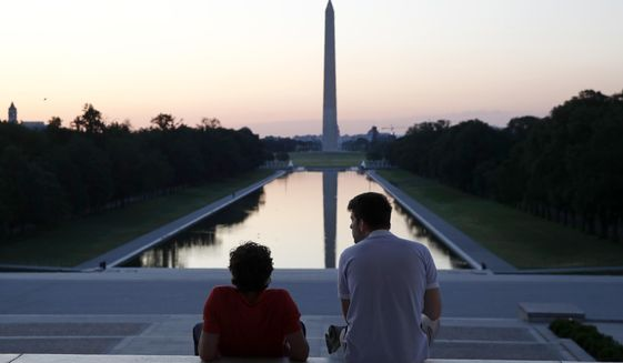 FILE - In this June 7, 2020, file photo, visitors watch sunrise from the Lincoln Memorial steps in Washington, the morning after massive protests over the death of George Floyd, who died after being restrained by Minneapolis police officers. (AP Photo/Patrick Semansky, File)
