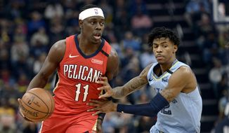 """In this Monday, Jan. 20, 2020 file photo, New Orleans Pelicans guard Jrue Holiday (11) handles the ball against Memphis Grizzlies guard Ja Morant in the first half of an NBA basketball game in Memphis, Tenn. The unusual resumption of the NBA season during the coronavirus pandemic is making mental health a priority. Pelicans guard Jrue Holiday expects basketball to be the easy part of living in the NBA's """"bubble"""" when 22 teams gather in Central Florida to resume their suspended seasons later this month. (AP Photo/Brandon Dill, File)  **FILE**"""