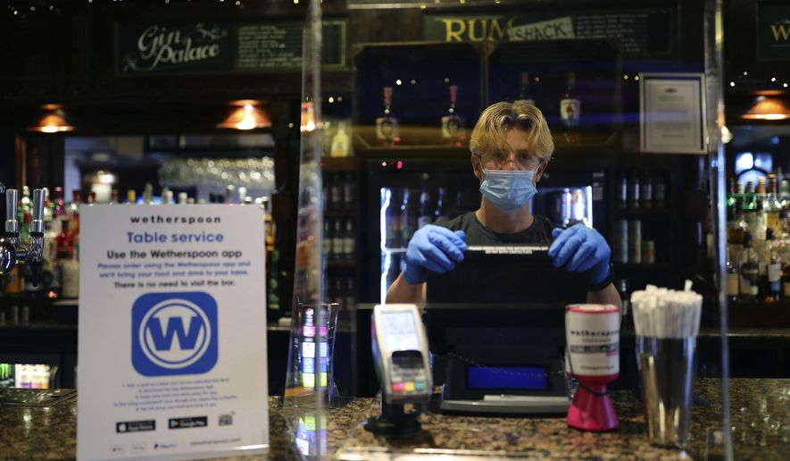 A member of staff wearing PPE, stands behind a screen as he waits to serve drinkers at the reopening The Toll Gate, a Wetherspoons pub in Hornsey, north London, as coronavirus lockdown restrictions are eased across the country, Saturday July 4, 2020. Restrictions which were imposed on March 23 have been eased allowing  businesses including pubs, restaurants and hair salons, to reopen to members of the public with measures in place to prevent the spread of the coronavirus. (Aaron Chown/PA via AP)