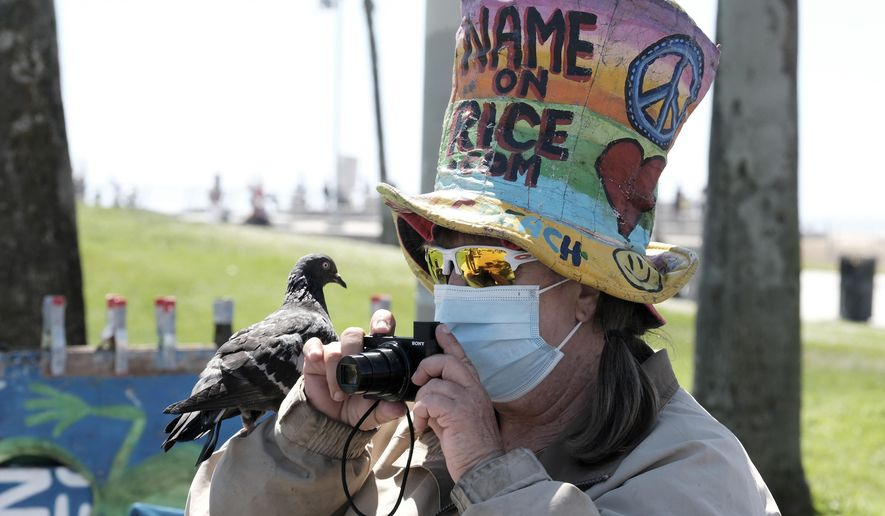 Vendor Vivianne Robinson, wearing a mask to protect from the coronavirus, takes a photo with a pigeon perched on her hand along the Venice Beach strand, Friday, July 3, 2020, in Los Angeles. California's governor is urging people to wear masks and skip Fourth of July family gatherings as the state's coronavirus tally rises. Newsom said he'd rely on people using common sense rather than strict enforcement of the face-covering order. (AP Photo/Richard Vogel)