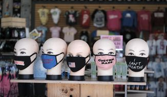 Facial masks are displayed at a shop at Venice Beach in Los Angeles, Friday, July 3, 2020. California's governor is urging people to wear masks and skip Fourth of July family gatherings as the state's coronavirus tally rises. But Gov. Gavin Newsom on Thursday said he would rely on people using common sense rather than strict enforcement of the face-covering order. Rates of COVID-19 infections and hospitalizations have soared in the past two weeks after falling last month. (AP Photo/Richard Vogel)