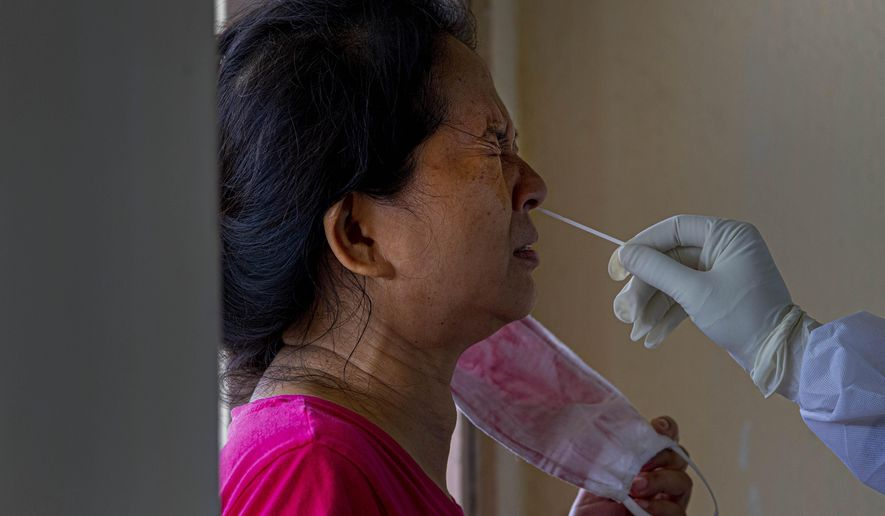 A woman grimaces as her nasal swab is being collected in Gauhati, India, Saturday, July 4, 2020. India's number of coronavirus cases passed 600,000 with the nation's infection curve rising and its testing capacity being increased. More than 60% of the cases are in the worst-hit Maharashtra state, Tamil Nadu state, and the capital territory of New Delhi. (AP Photo/Anupam Nath)