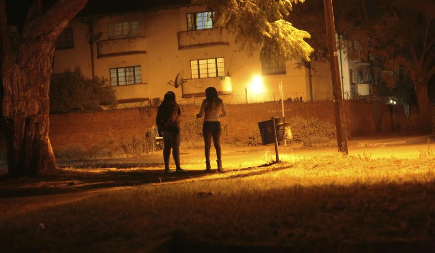Sex workers wait for clients in the red light district of Harare, Zimbabwe, Friday, June 12, 2020. As the coronavirus spreads in Africa, it increasingly threatens those who earn their living on the streets, including sex workers with HIV. (AP Photo/Tsvangirayi Mukwazhi)