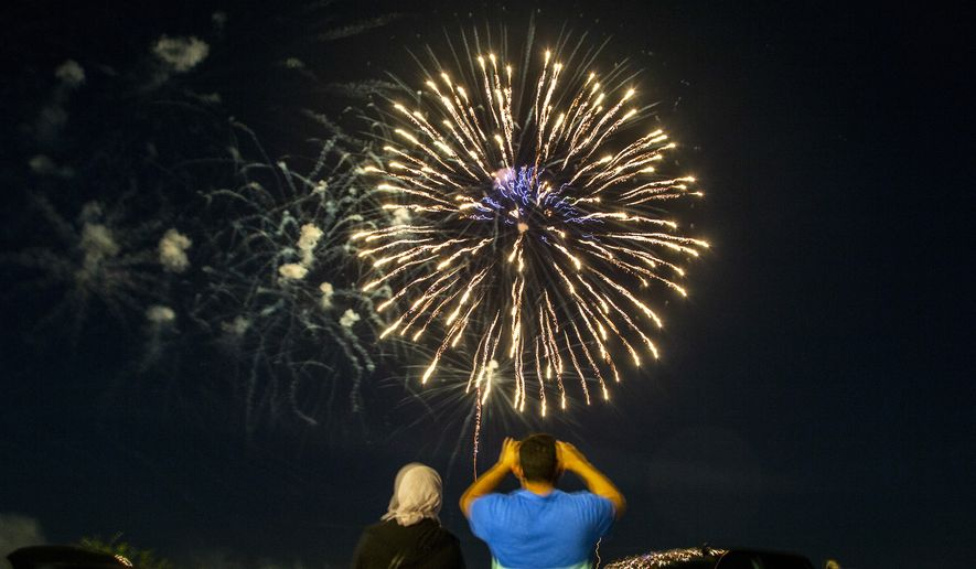 A family takes photos as fireworks explode during the Coralville 4th Fest drive-in fireworks show amid the novel coronavirus pandemic, Saturday, July 4, 2020, in Coralville, Iowa. (Joseph Cress/Iowa City Press-Citizen via AP)