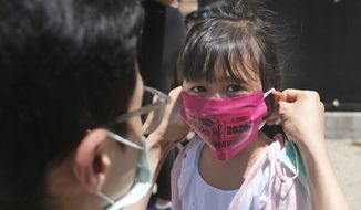 In this June 10, 2020, file photo, Olivia Chan's father helps her with a new mask she received during a graduation ceremony for her Pre-K class in front of Bradford School in Jersey City, N.J. (AP Photo/Seth Wenig, File)